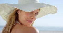 Close up of Beautiful woman walking on beach looking back at camera smiling Stock Footage