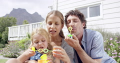 Happy family blowing bubbles in the yard at home Stock Footage