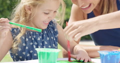 Happy family  with little girl painting in the yard Stock Footage