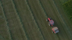 Aerial, vertical - Tracking shot of a tractor collecting the grass to make bale - stock footage