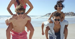 Beach couples giving piggybacks laughing having fun on vacation - stock footage