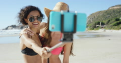 Two friends taking selfies on the beach using selfie stick Stock Footage