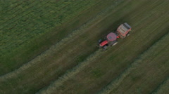 Aerial, vertical - Tractor unloads bale and continues to collect the grass Stock Footage