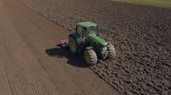 Aerial - Farm machinery with a rolling harrow smoothing out the soil Stock Footage