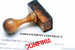 Employment contract and rubber stamp - stock photo