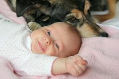 Happy Newborn Baby Snuggling with Pet Dog - stock photo