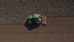 Aerial, vertical - Tractor with a rolling harrow making soil loose for seeding - stock footage