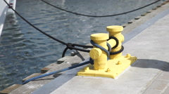 Harbor quayside yellow mooring bollard with rope Stock Footage