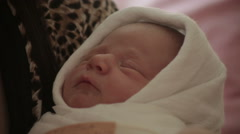 Newborn baby sleeping and dreaming in mother arms, infant face close up. - stock footage