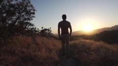 Man does a Flip and Walks into Sunset along Mountain line in Slow Motion. Stock Footage