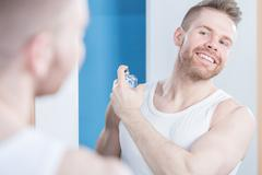 Handsome guy applying perfume - stock photo