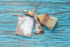Paintbrush  trowel sandpaper  still life wood teak table antique blue old sty Stock Photos