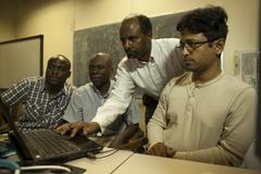 Students collaborating with professor university campus - stock photo