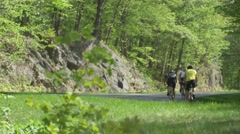 Cyclists riding up hill-Pan shot Stock Footage