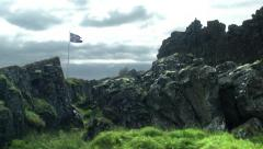 Icelandic Flag Flying Over Moss Covered Stones in ICELAND  Stock Footage