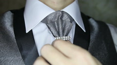 Groom corrects brooch on dark silver necktie Stock Footage