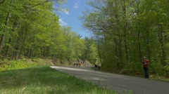 Group of longboarders speed down hill Stock Footage