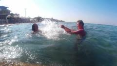 Entertainment on the sea man and woman splashing in water Stock Footage