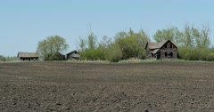 Stock Video Footage of Run-down abandoned farm house and barn on the prairies.