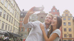 Couple taking self portrait selfie photo having fun laughing in Stockholm Stock Footage