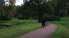 Old woman with crutches disabled person goes through the park Stock Footage