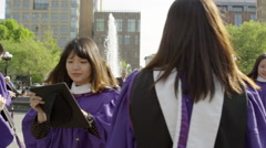 NYU Washington Square Park female Asian graduates cap and gown slow motion 4K Stock Footage
