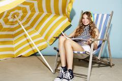 Girl on deckchair ready for vacation Stock Photos