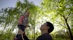 Young asian father lovingly holding up cute baby while they play together Stock Footage