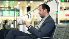 Young businessman using smartphone while sitting at train station HD - stock footage