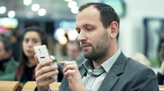 Stock Video Footage of Young businessman using smartphone while sitting at train station HD