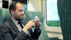 Young businessman watching something on smartphone while sitting at train HD Stock Footage