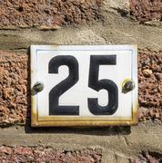 Enameled house number twenty five. - 25 - stock photo