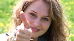 Playful woman thumbing up Stock Footage