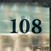 House number one hundred and eight, engraved in an reflective metal plate. - 108 - stock photo