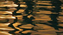 Warm Light Reflecting Off the Surface of Gentle Water Ripples. - stock footage