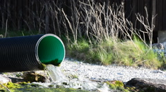 Sewer pipe pushing dirt water into the ocean Stock Footage
