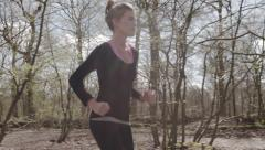 Woman exercising runs through a forest in a park full of trees with sun flares - stock footage