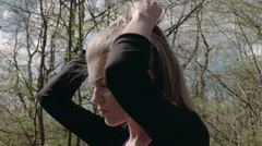 A young woman ties her hair then prepares herself for a run through a forest - stock footage
