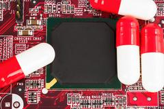 Close-up of an integrated  circuit and medical pill - stock photo