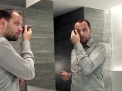 Man applying anti wrinkle roll-on on his skin in bathroom  NTSC Stock Footage