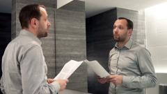 Young businessman trying his speech in front of the mirror in bathroom HD Stock Footage