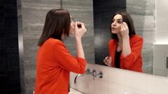 Young beautiful woman applying makeup on eyebrow in bathroom HD Stock Footage