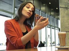 Stock Video Footage of Pretty woman applying mascara eyelash sitting in cafe NTSC