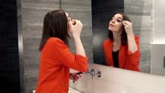 Stock Video Footage of Pretty woman applying mascara eyelash in front of the mirror in bathroomHD