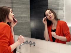 Pretty woman applying anti wrinkle roll-on on her skin in bathroom  NTSC Stock Footage