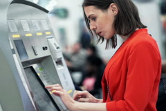 Young woman buying ticket from vending machine at station NTSC Stock Footage