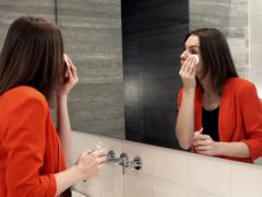 Pretty woman cleaning face with cotton swab in bathroom  NTSC Stock Footage