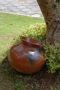 Shiny brown terracotta pot in garden Stock Photos