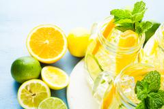 Infused water with fresh citrus fruits and ice Stock Photos