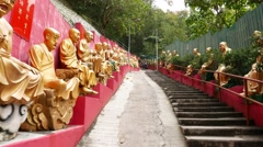 Climb up way to monastery, many gold Buddha statues on the way - stock footage
